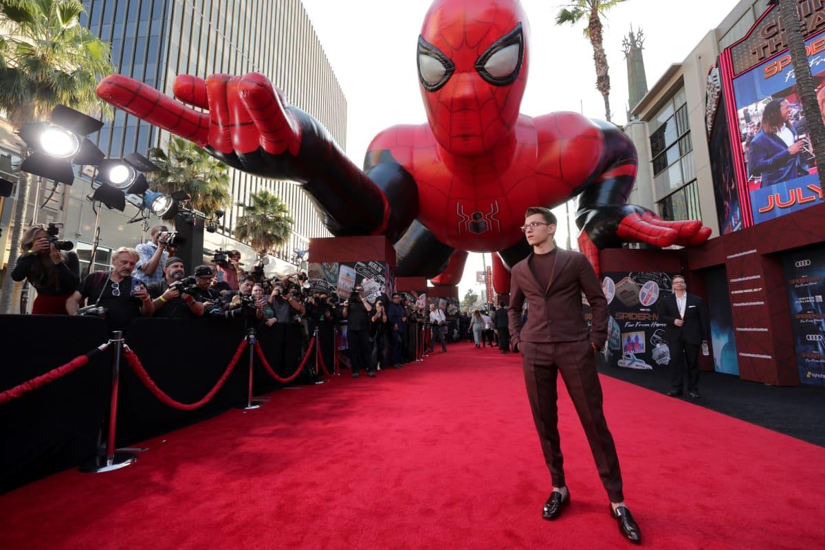 Tom Holland punaisella matolla suuren Hämähäkkimies-veistoksen edessä.