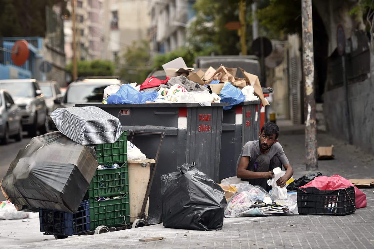 Mies käy läpi roskia kadulla Beirutissa.