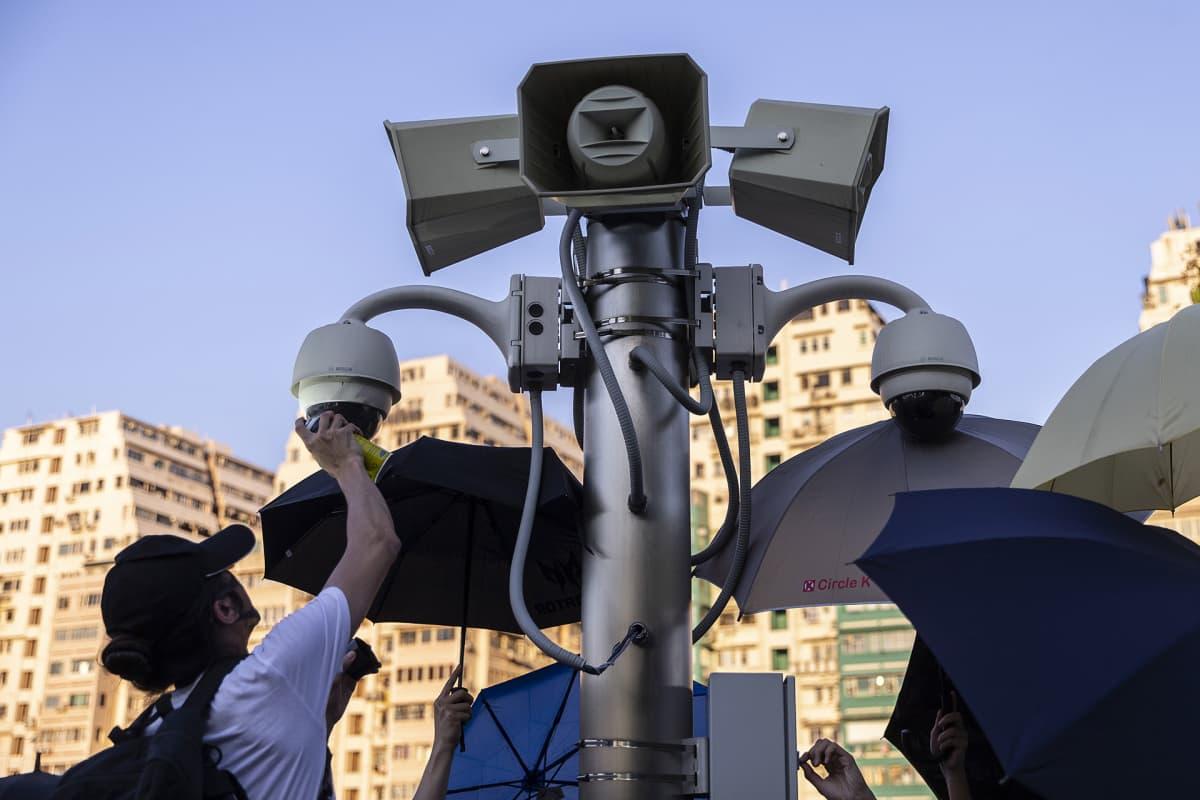 mies spreijaamassa valvontakameraa