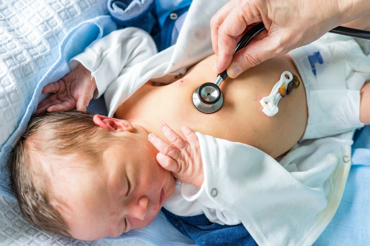 Vastasyntynyttä tutkitaan stetoskoopilla.