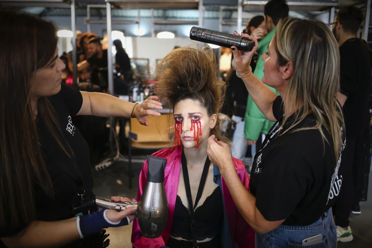 Malli meikataan ja kammataan kulisseissa muotinäytöksessä Portossa, Portugalissa, 23. lokakuuta. Kevät / kesä 2020/21 -mallistot esitellään Portugalin 44. muotipäivillä 26. lokakuuta asti.