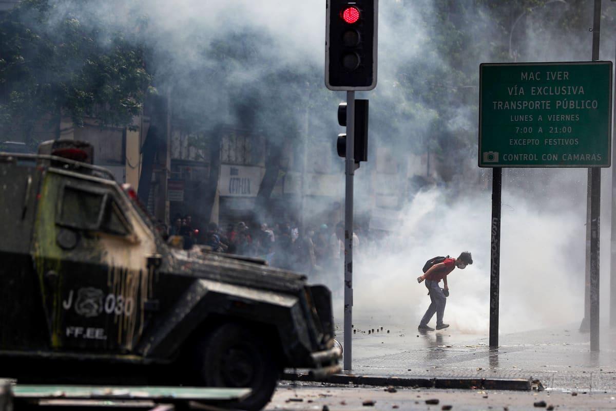 Mielenosoittajat ottavat yhteen poliisin kanssa hallituksen vastaisten mielenosoitusten kuudentena päivänä, Santiagossa, Chilessä, 23. lokakuuta. Chilen pääkaupungin metrolipun hinnan nousu merkitsi mielenosoitusten aallon alkua, joka päivien kuluessa siirtyi nopeasti laajempaan protestiin sosiaalista eriarvoisuutta vastaan. Chilen sisäasiainministeriön apulaissihteeri Rodrigo Ubilla vahvisti, että kuolonuhrien määrä maassa 18. lokakuuta alkaneiden mielenosoitusten aikana nousi kahdeksaantoista uhriin.
