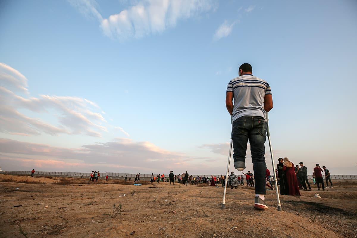 Palestiinalainen mies jonka toinen jalka on amputoitu osallistuu mieleosoitukseen Israelin ja Gazan rajalla 25. lokakuuta.