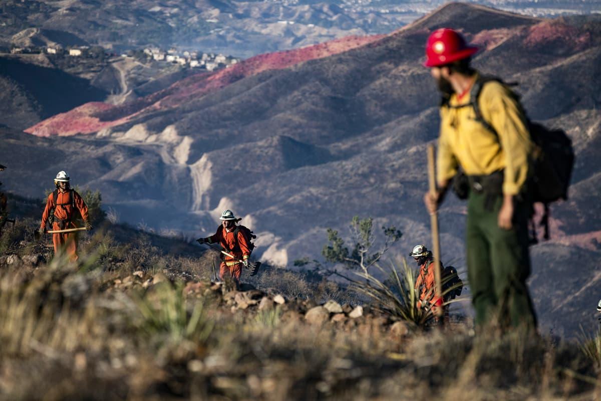 Palomiehiä (keltainen paita) ja vankeja (oranssi asu) menossa sammuttamaan maastopaloa Agua Dulce kukkulalle lähellä Santa Claritaa Kaliforniassa 25. lokakuuta.