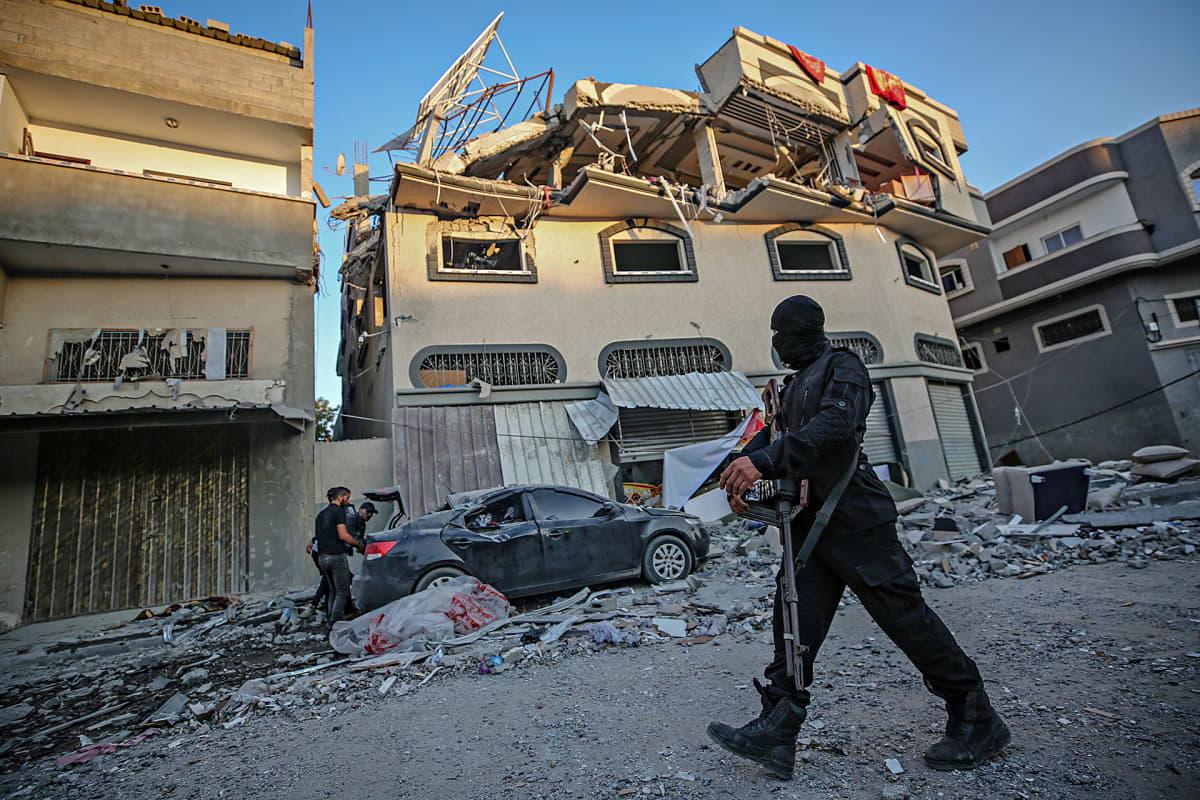 Islamistijohtaja Baha Abu Al-Atan vahingoittunut talo Gazassa 12. marraskuuta 2019. JIhad-sotilas vartiossa ulkopuolella.