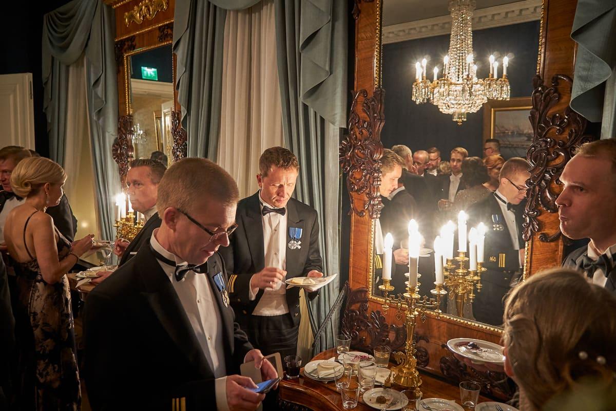 Ihmiset syövät ja juovat Linnan juhlissa.