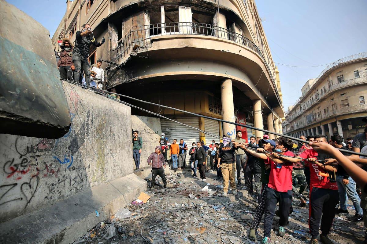 Irakilaiset mielenosoittajat kiskovat betonielementtejä köysillä pystyyn Bagdadissa 29. marraskuuta.