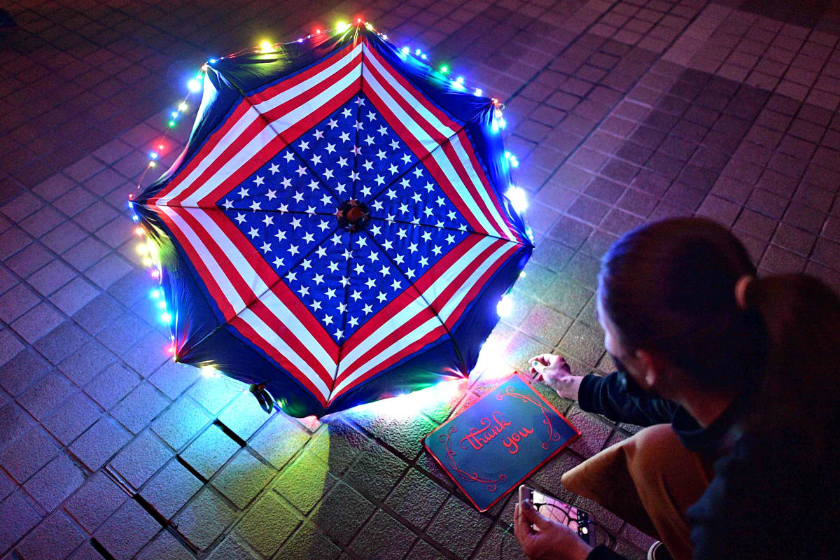 Sateenvarjossa ovat Yhdysvaltain lipun värit ja symbolit. Sateenvarjo on koristeltu jouluvaloilla ja katukivetyksellä on kiitos kirjoitettuna englanniksi mustalle, pienelle taululle.