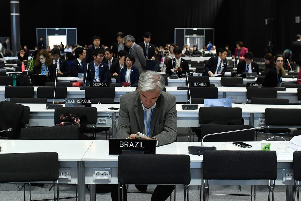 Ilmastokokouksen osallistujia kuvattuna COP25-tapahtumassa odottamassa viimeisen istunnon alkamista Madridissa 15. joulukuuta.