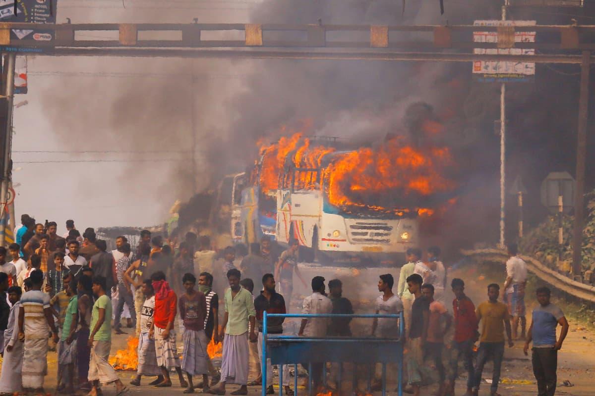 Mielenosoittajia Kolkatassa 14. joulukuuta. Bussi tulessa ja paljon ihmisiä