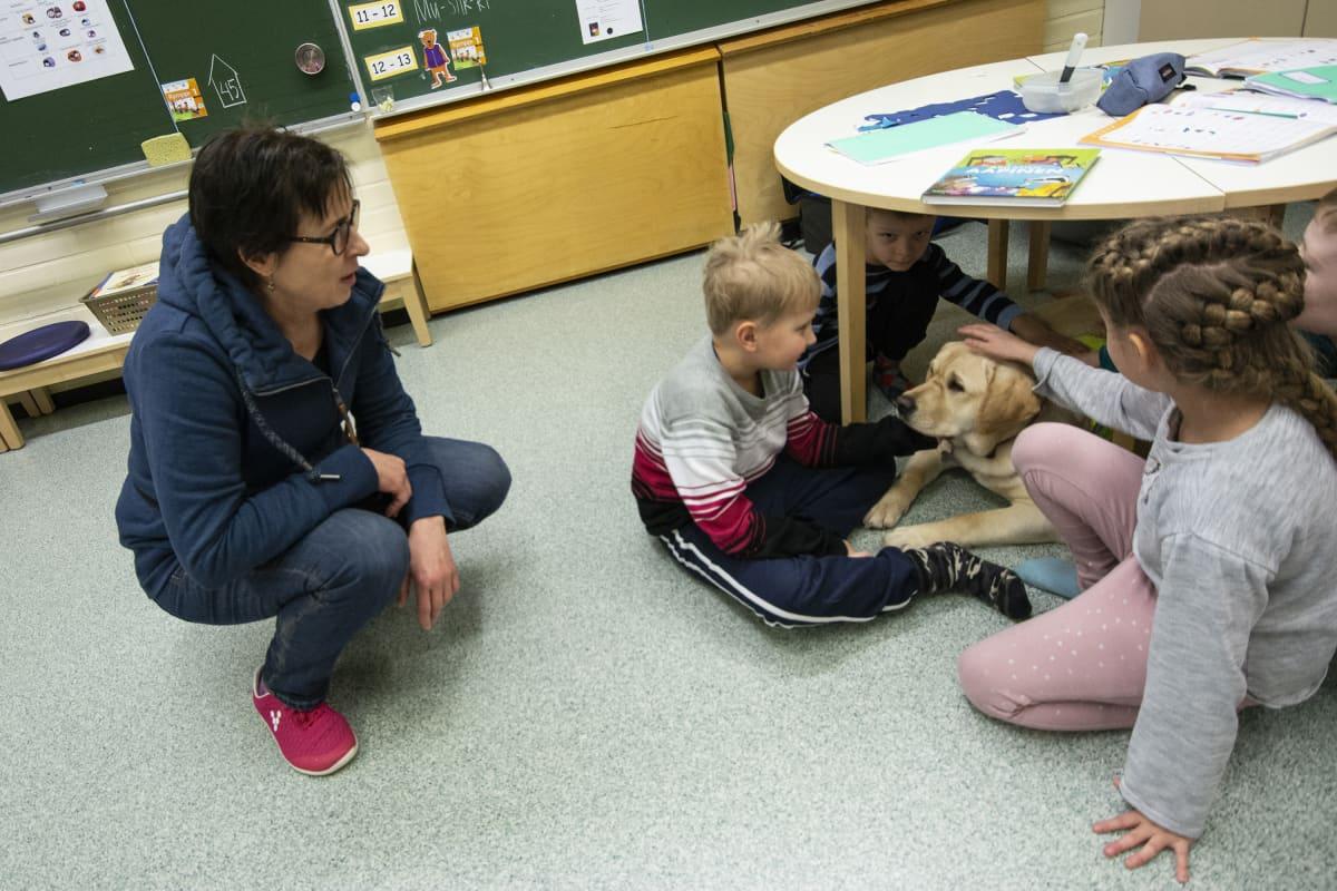 Ruuti-koira yhdessä oppilaiden kanssa.