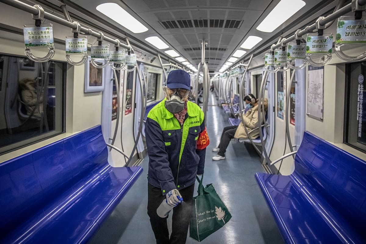 A subway worker wearing a protective face mask and eyewear disinfects a subway carriage in Beijing, China, 10 February 2020. Major China's cities began going back to work after the Lunar New Year holiday, which was extended in an attempt to contain the spread of the deadly coronavirus across the country.