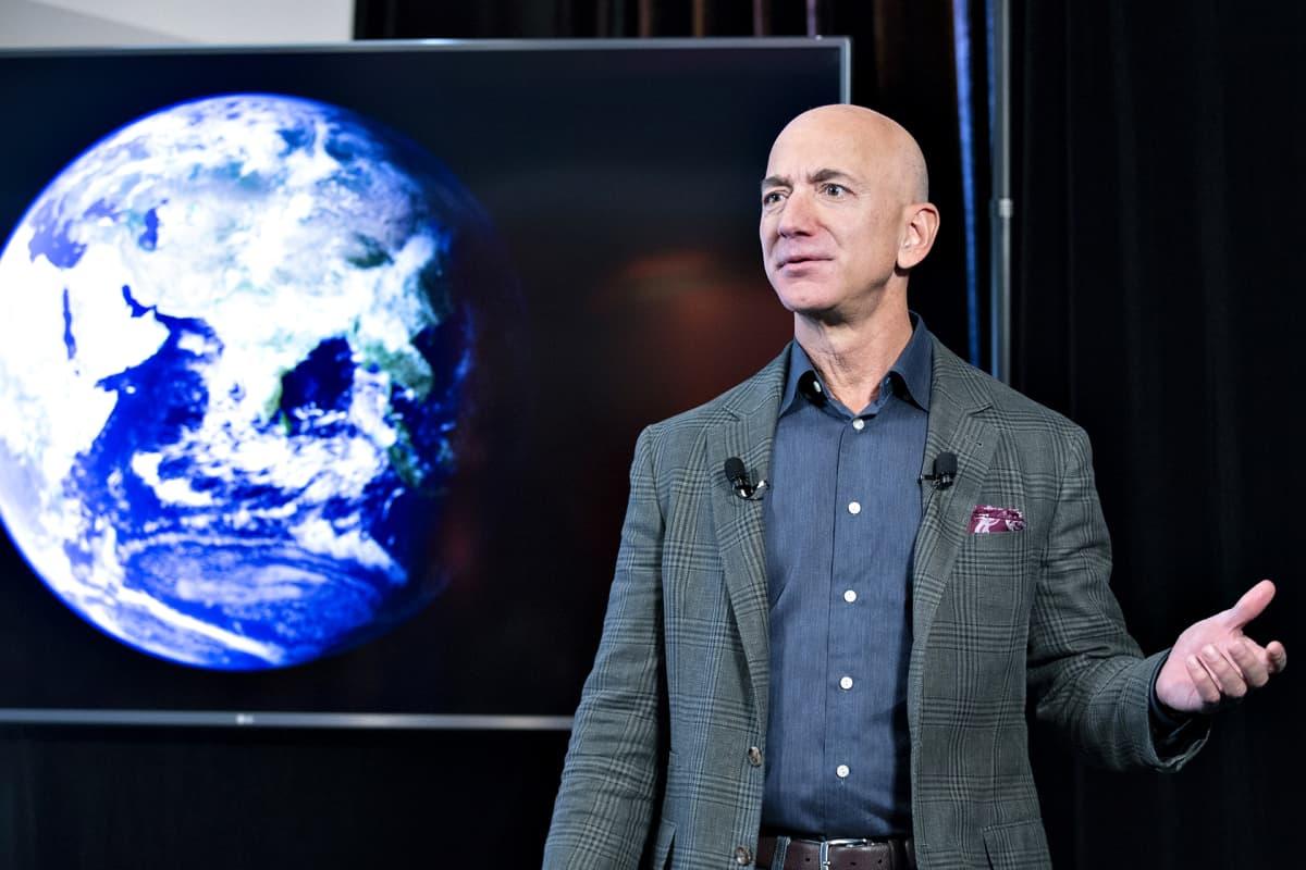 Jeff Bezos pitää puhettaan. Taustalla on maapallo kuvattuna avaruudesta.