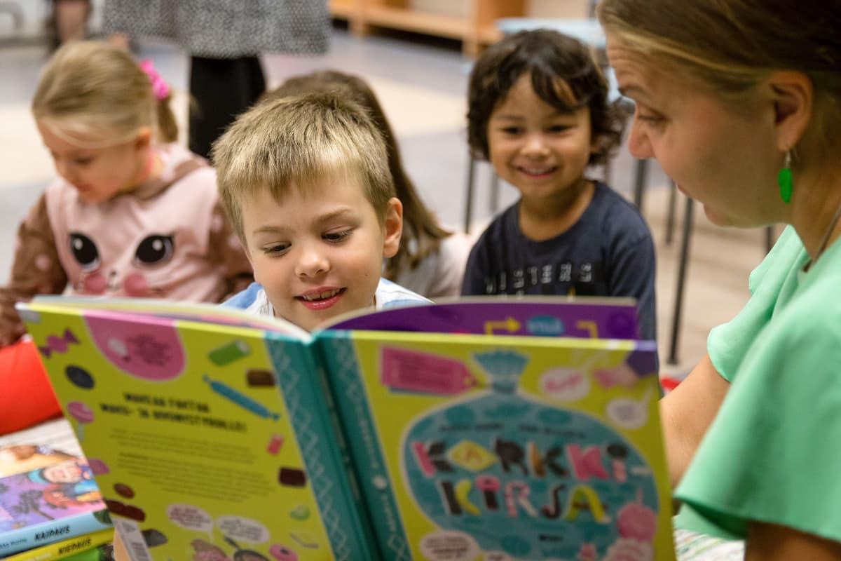 Lapsia lukemassa kirjoja kirjastossa.