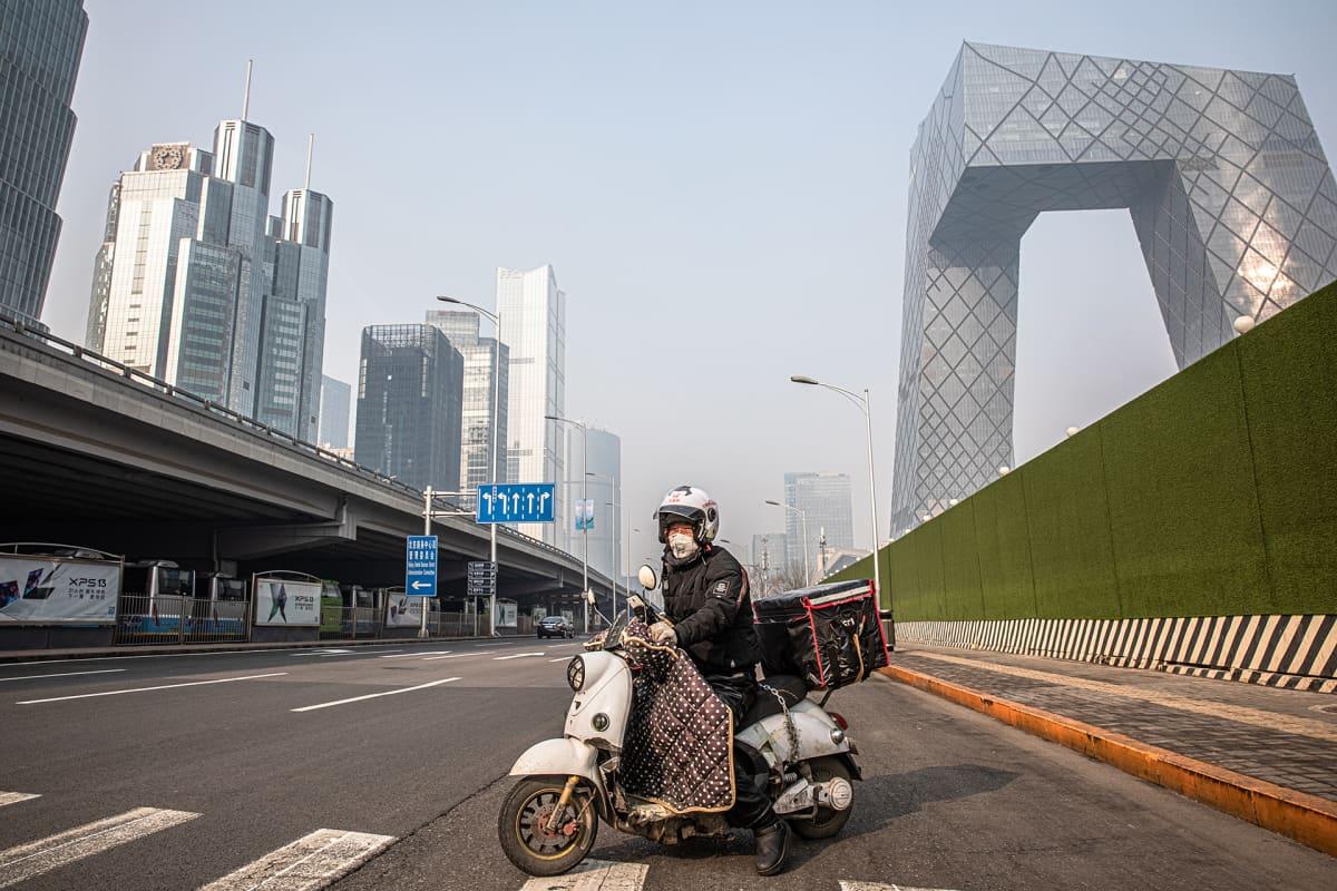 Ruokalähetti skootterin päällä tyhjällä kadulla Pekingin liike-elämän keskuksen kupeessa.