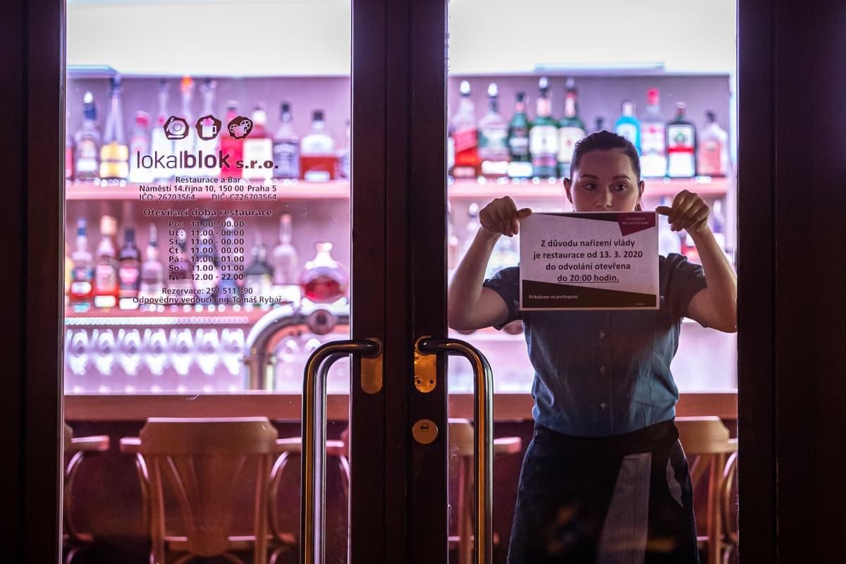 Tarjoilija kiinnittää ravintolan oveen ilmoitusta sulkemisesta Prahassa.