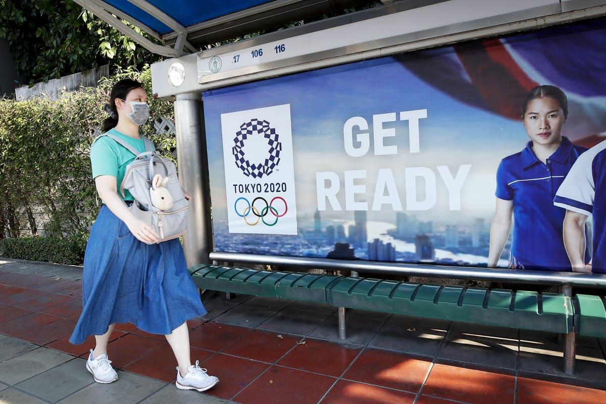 Nainen kävelee bussipysäkillä olevan Tokion olympialaisten mainoksen ohi Bangkokissa.