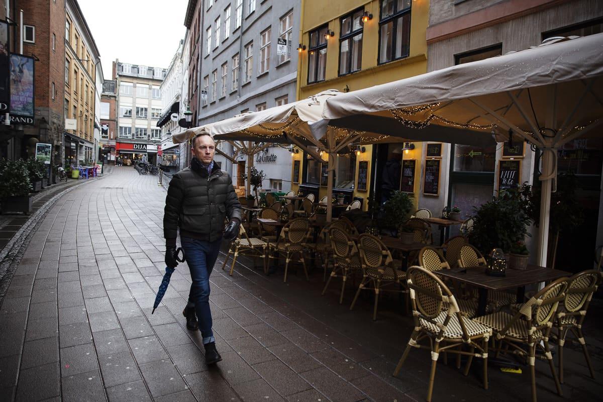 Mies kävelee tyhjällä kadulla.