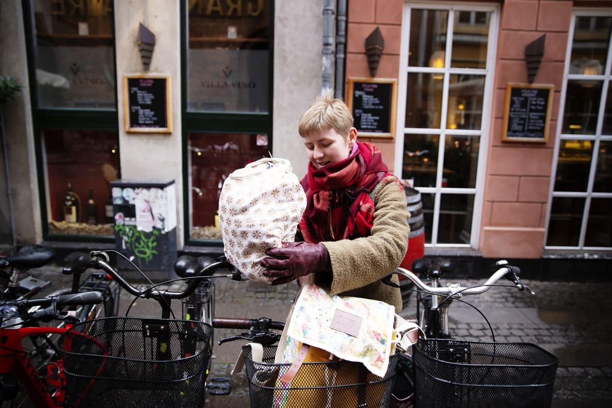 Nainen asettaa kassia polkupyörän koriin.