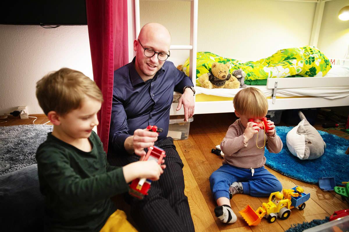 Lapset leikkivät isän kanssa.