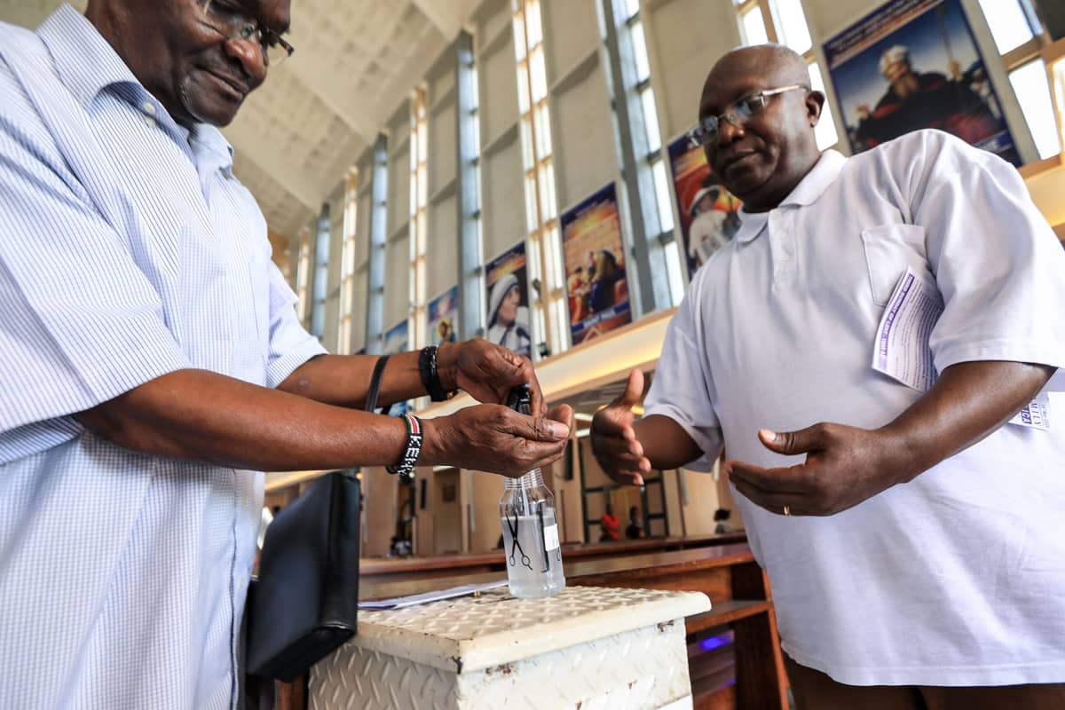 Kenialaiset miehet desifioivat kätensä ennenkuin poistuvat kirkosta Nairobissa 13. maaliskuuta.