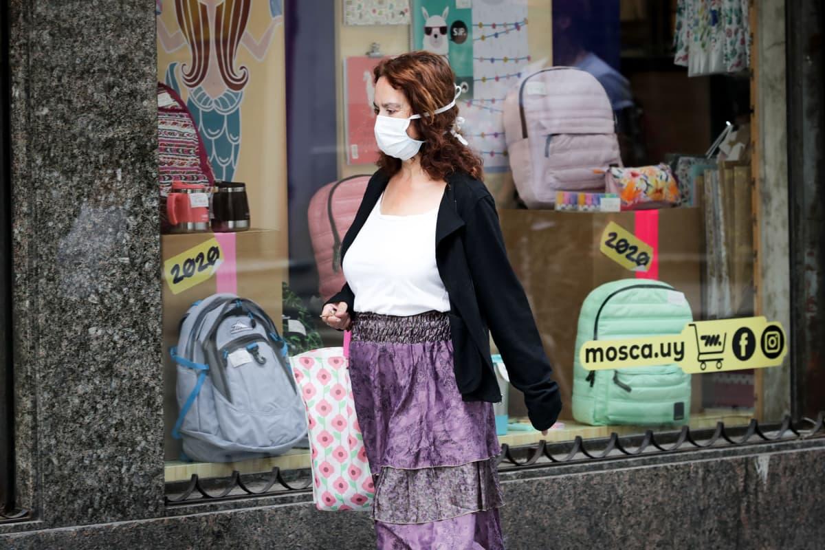 Naisella hengityssuojain kasvoillan Montevideossa.