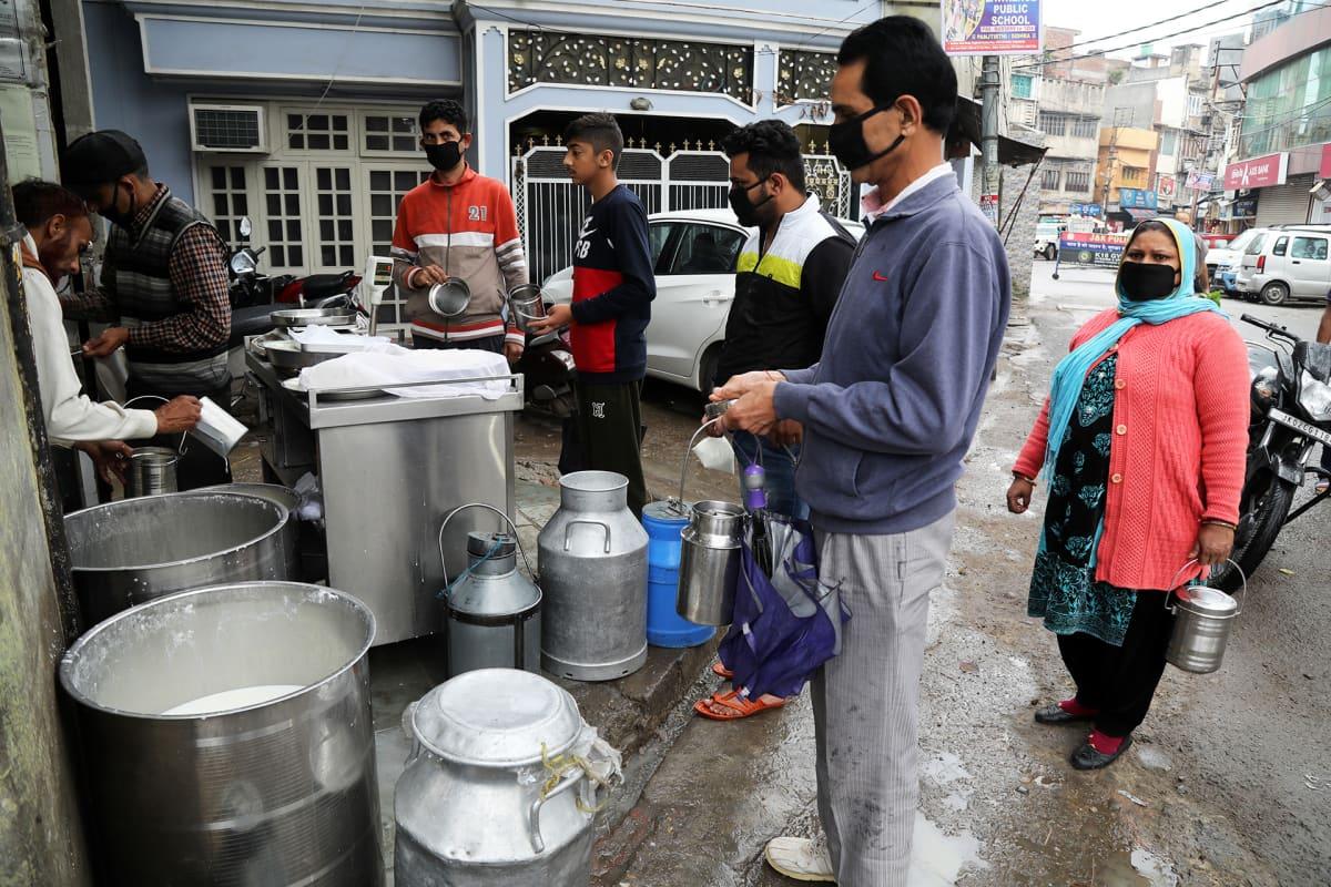 Miehiä ostamassa maitoa Jammussa Intiassa.