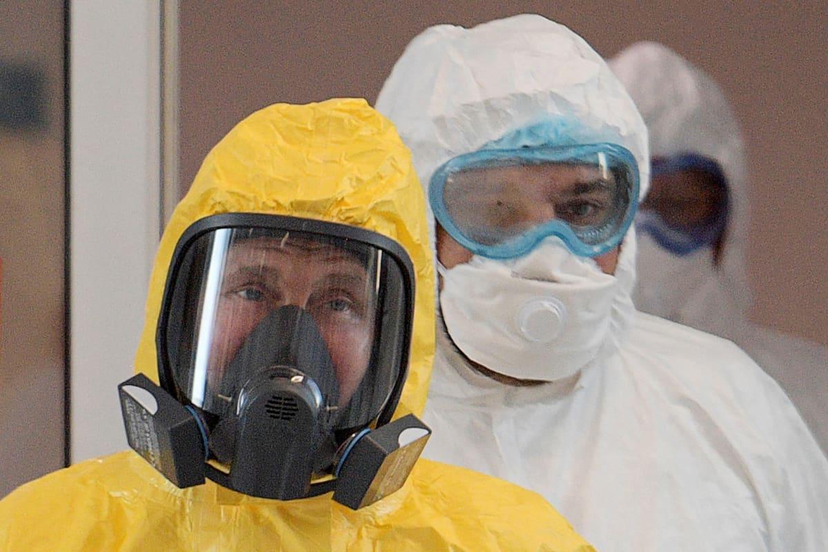 Vladimir Putin suojavaatteissa sairaalakäynnillä Kommunarkassa.