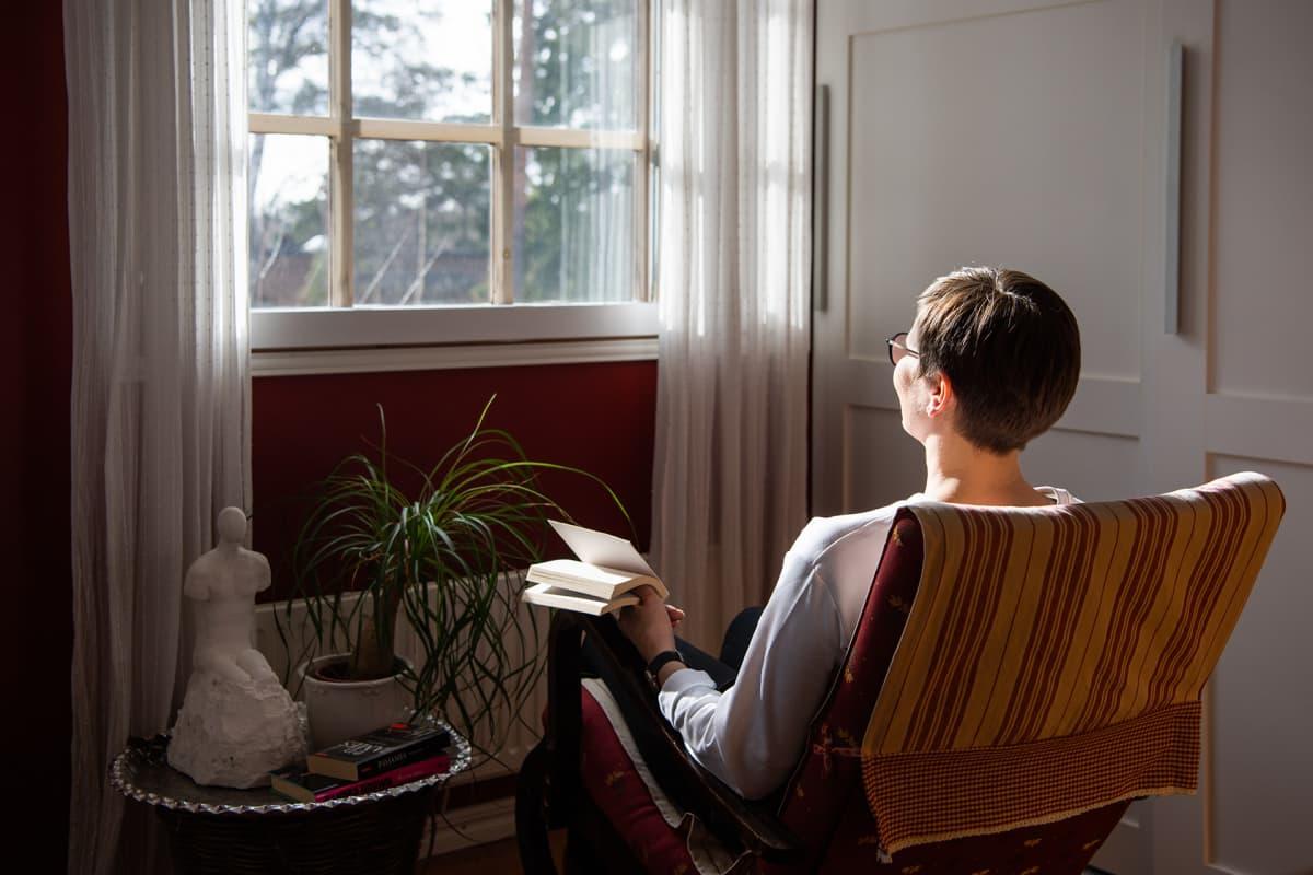 Nainen katselee ikkunasta ulos kirja kädessään.