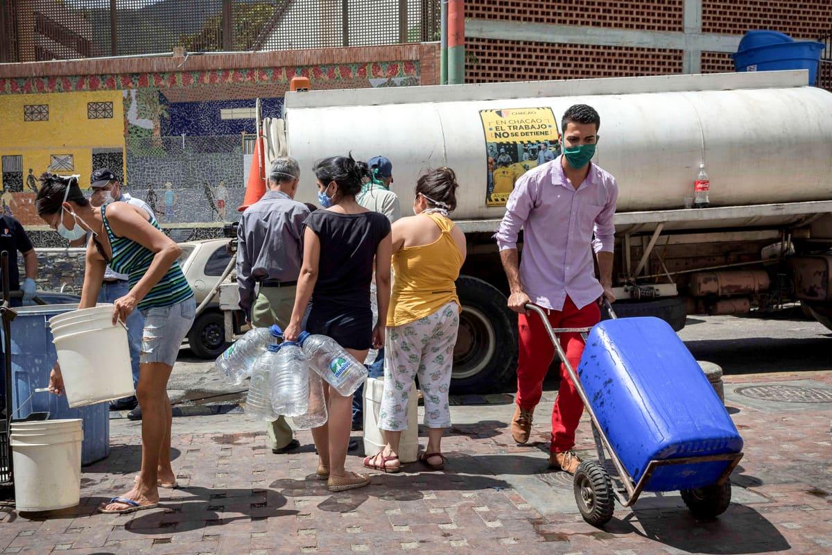 Ihmiset jonottavat saadakseen juomavettä tankkiautosta.