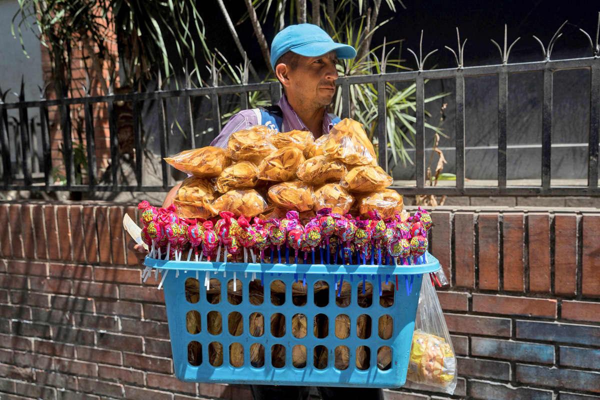 Katumyyjää kantaa koria jossa mm. bananneja myynnissä.
