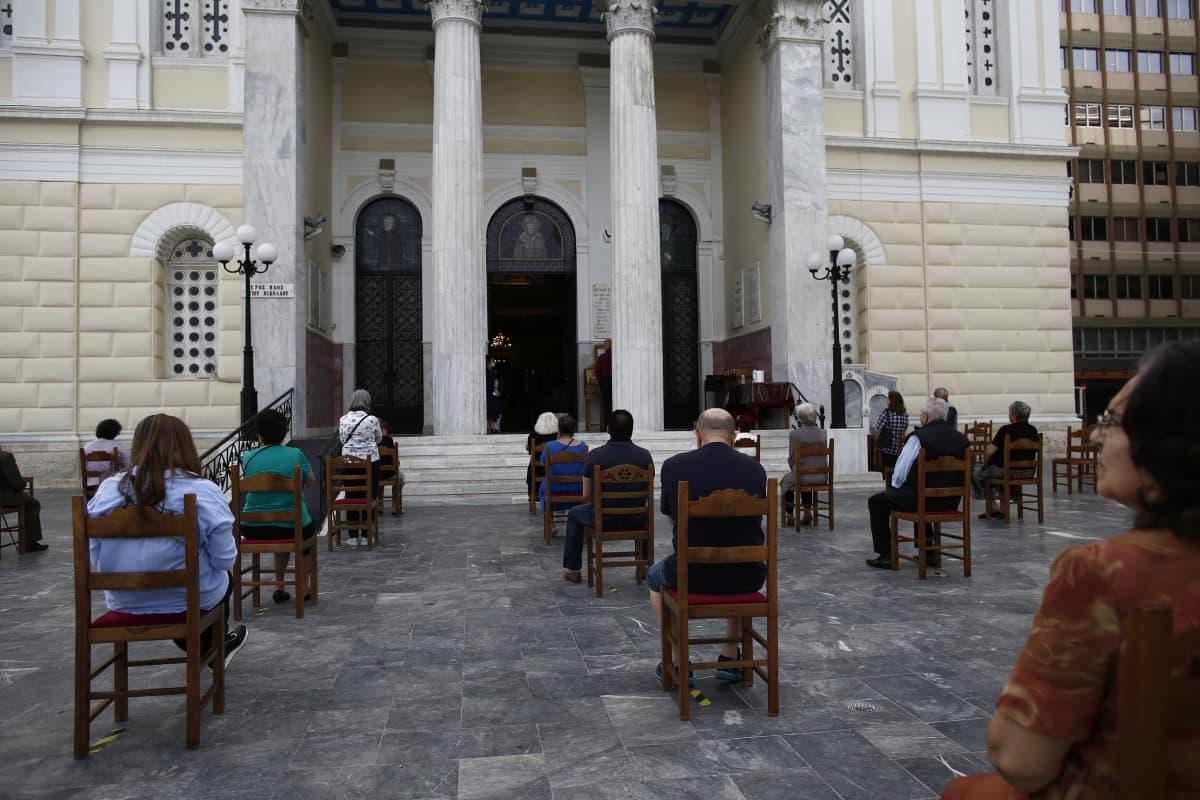 Jumalanpalvelusta pidetään turväväleillä kirkon ulkopuolella Pireuksesas Kreikassa.