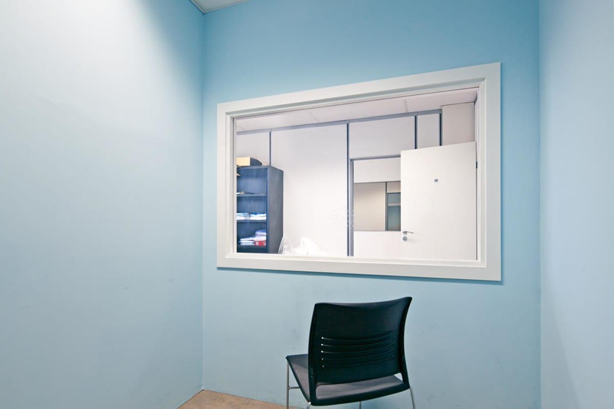 Valokuvateos, jossa näkyy huoneen siniset seinät, musta tuoli ja ikkuna toiseen huoneeseen.
