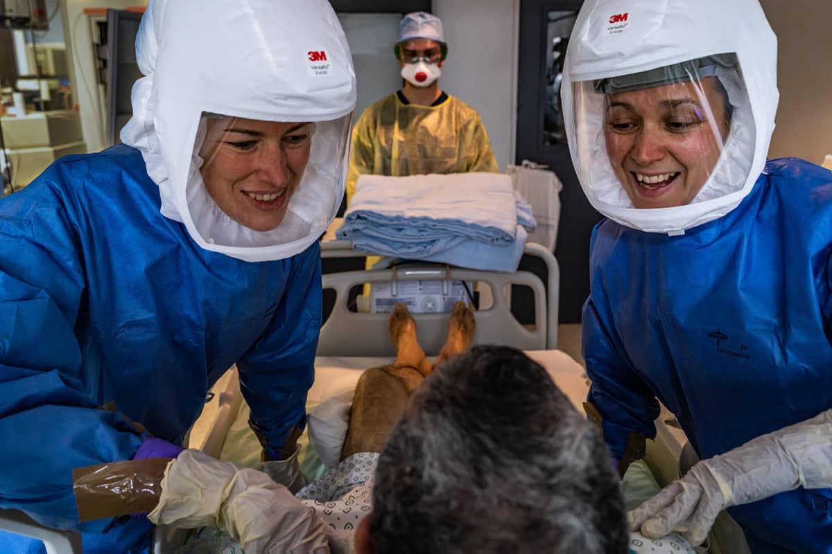 Valokuvateos, jossa kaksi potilasta hoitavaa naista hymyilevät potilaalle.