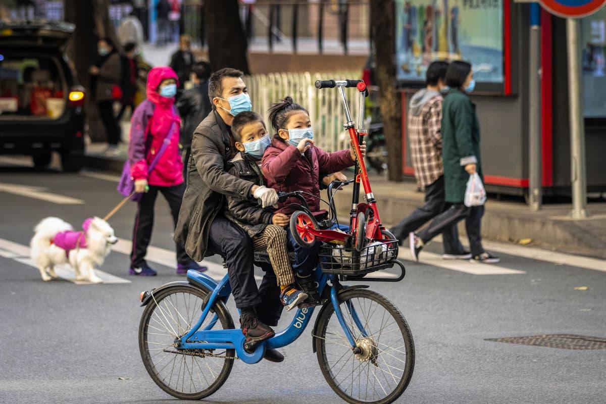 Isä kahden lapsensa kanssa polkypyörällä.