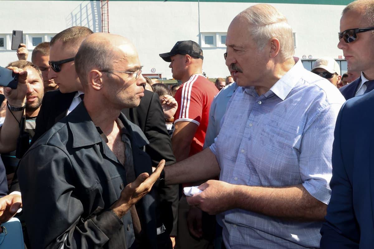 Valko-Venäjän presidentti Alexander Lukashenko keskustelee tehtaan työtekijän kanssa. Lukashenko piti puheen rengastehtaalla 17. elokuuta.