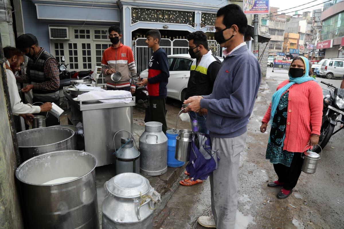 Ihmisiä ostamassa maitoa Pohjoiis-Intiassa ulkonaliikkumiskiellon aikana maaliskuussa 2020.
