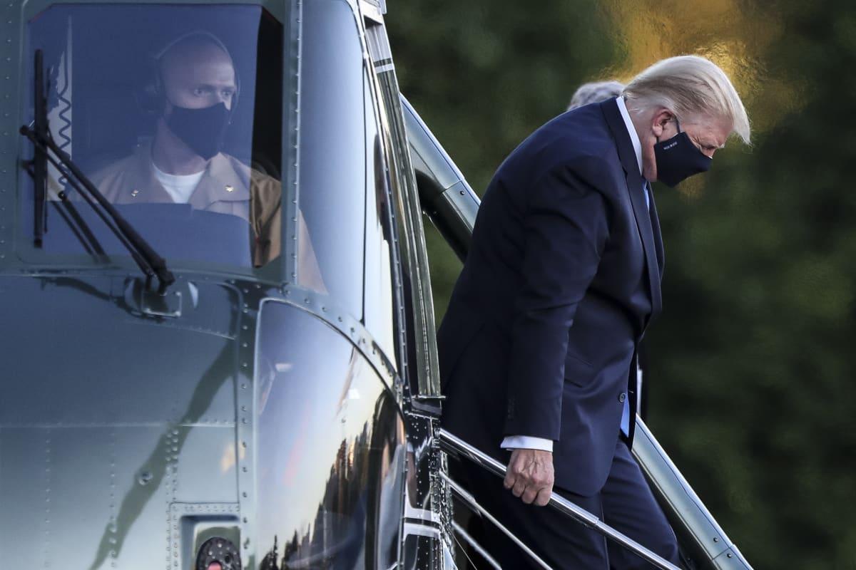 Donald Trump poistumassa helikopterista.