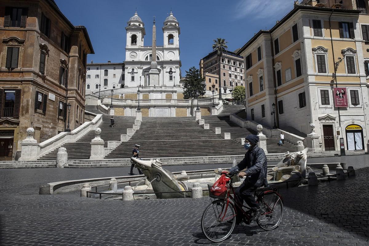 Espanjalaiset portaat tyhjillään, etualalla yksinäinen pyöräilijä.