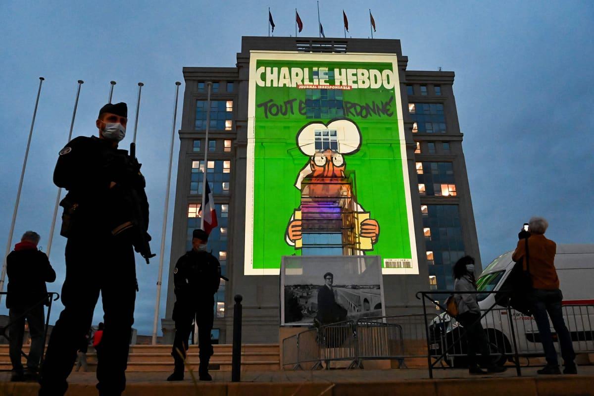 Aseistetut poliisit vartioivat Hotel de Regionin edustaa Montpellierissa kun rakennuksen julkisivuun heijastetaan Charlie Hebdon pilakuvia.