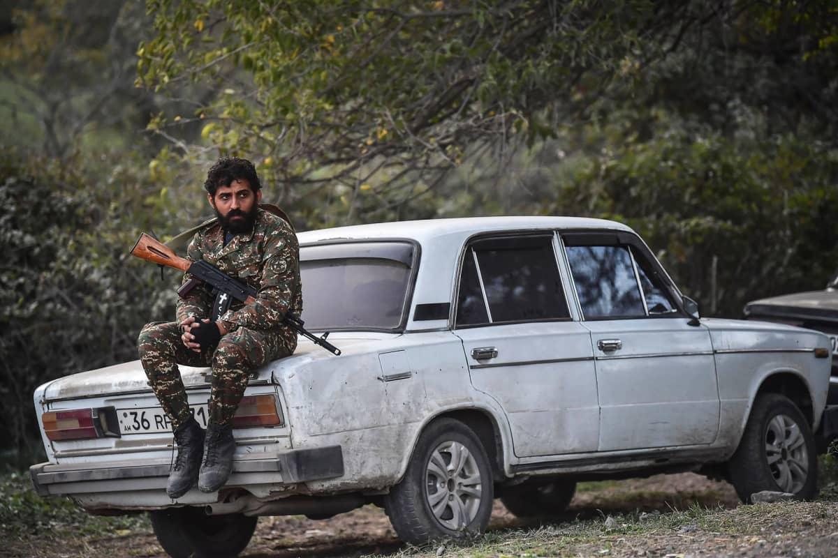 Vapaaehtoinen taistelija istuu auton takakontilla.
