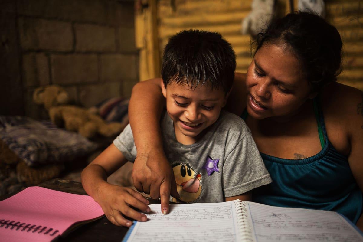 Äiti opettaa poikaansa kotona