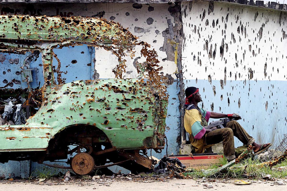 LURD:n sissi istuu luodinreikiä täynnä olevan seinän vierellä Monroviassa Liberiassa.