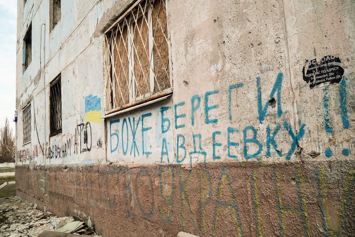 """""""Jumala, pelasta Avdijivka"""", lukee kerrostalon seinässä. Viereen on maalattu Ukrainan lippu."""