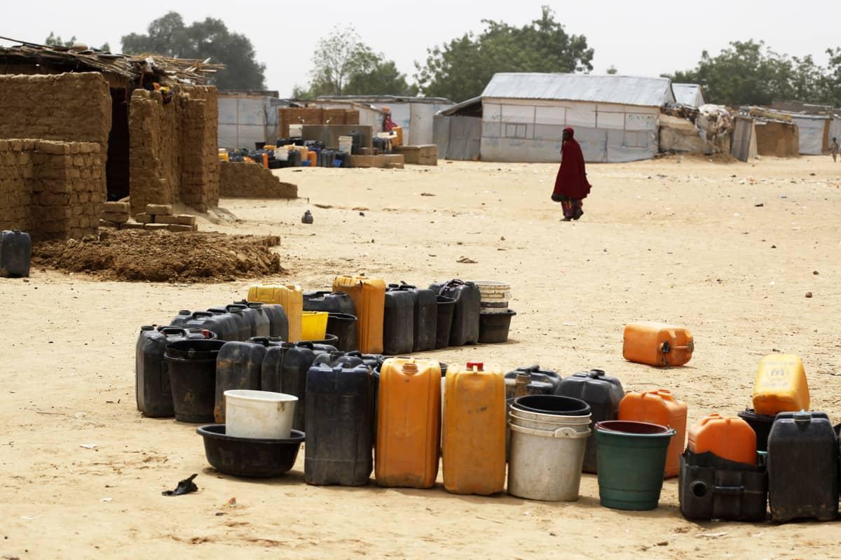 Vesikanistereita jonossa pakolaisleirillä Nigeriassa.