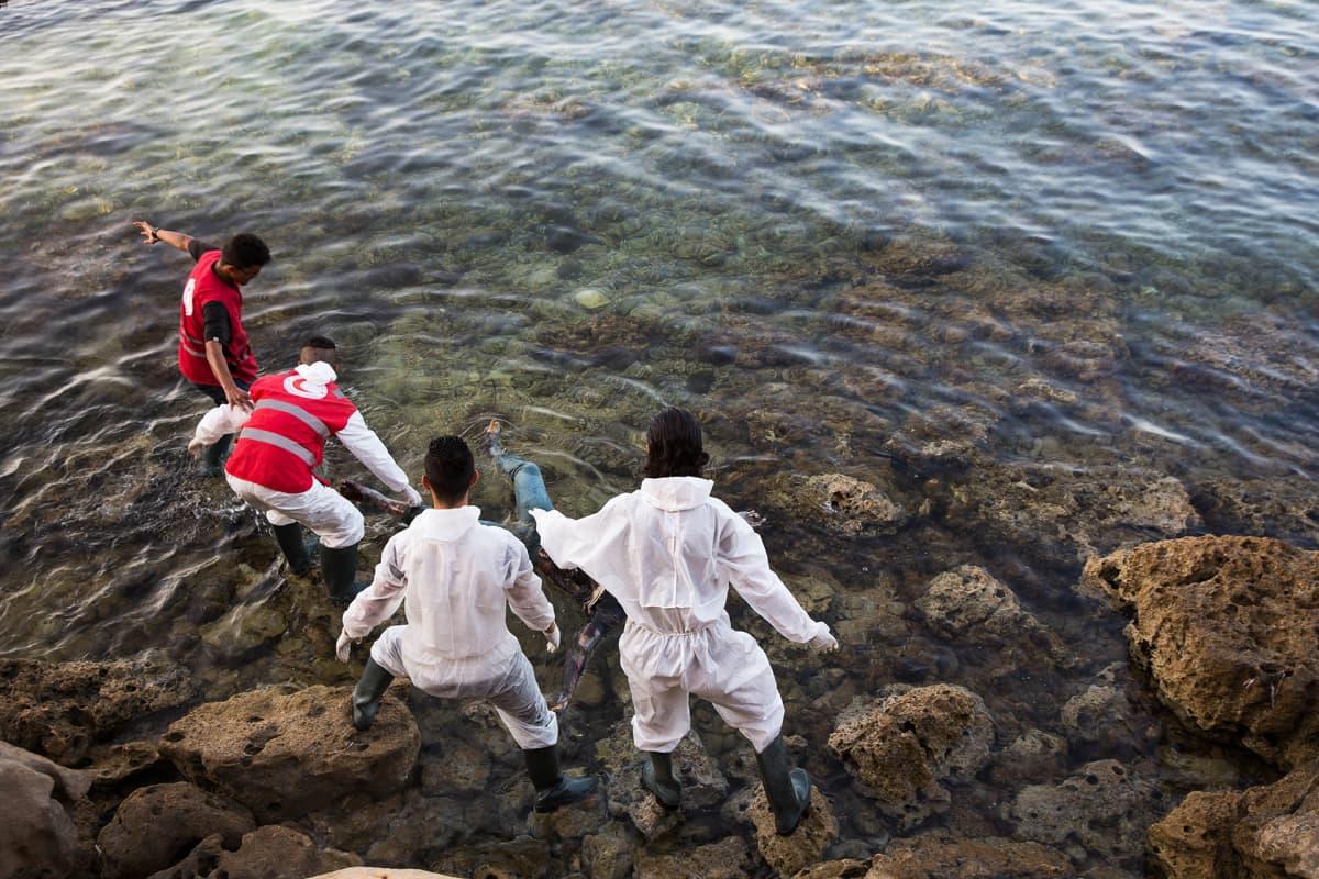Libyan Punaisen puolikuun työntekijät etsivät rannoilta hukkuneiden pakolaisten ruumiita Tajourassa Tripolin itäpuolella heinäkuussa 2017.