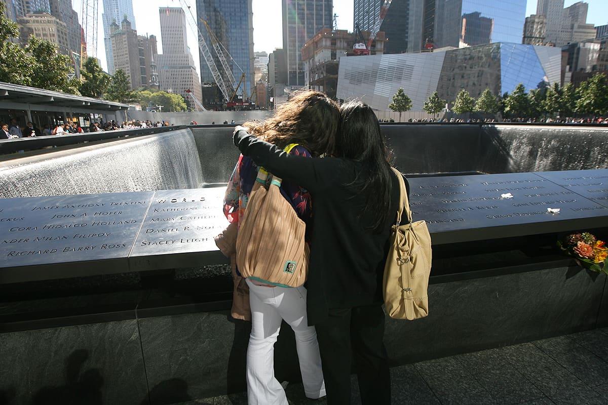 Kaksi naista lohduttaa toisiaan World Trade Centerin iskujen muistopaikalla.