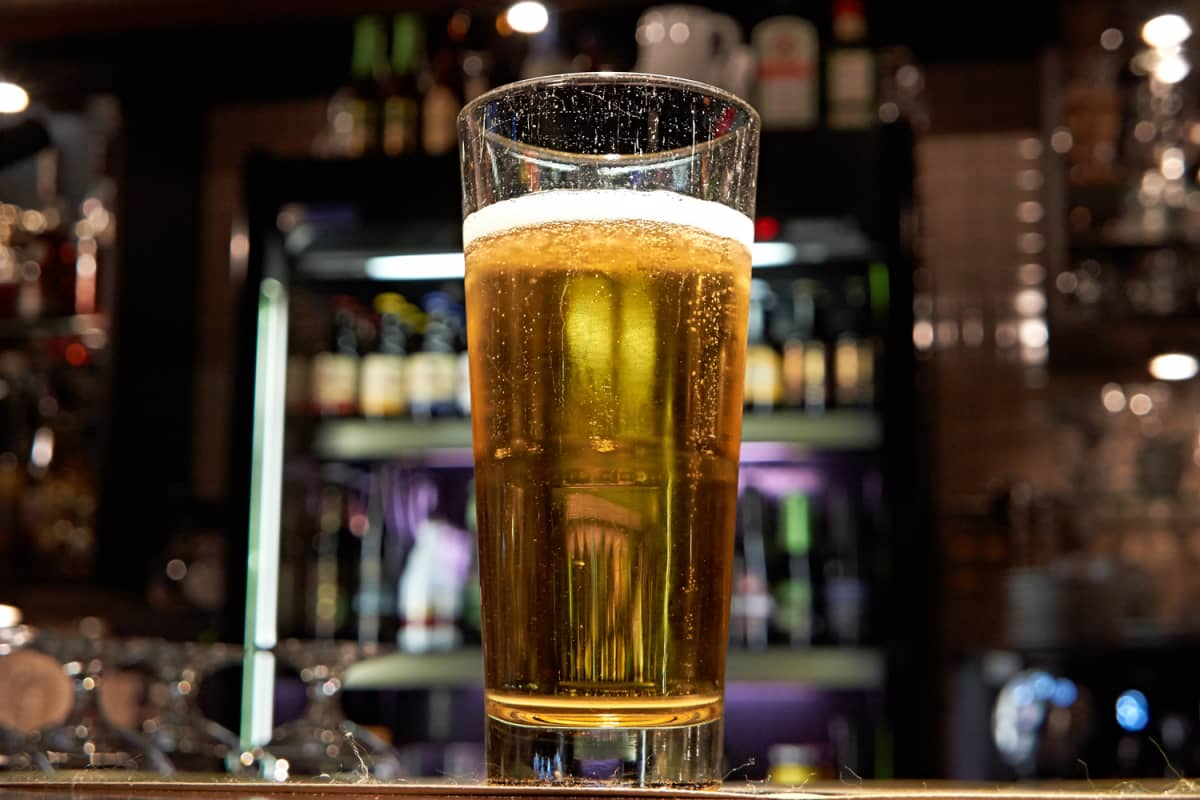 A glass of beer on a bar.