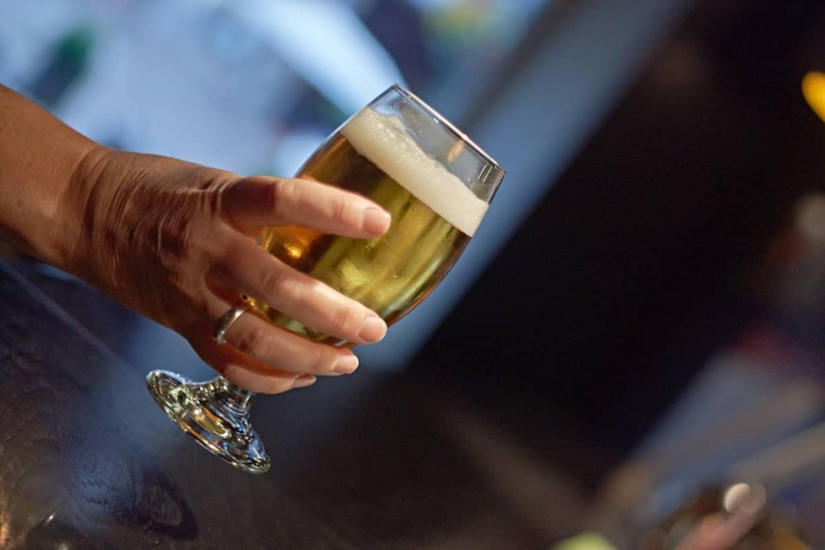 Glass of beer held in a woman's hand.