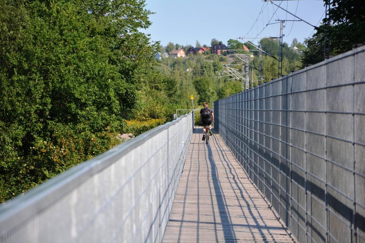 Pyöräilijä ylittää rautatiesiltaa